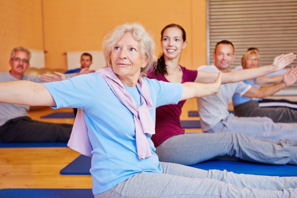 Seniorin macht Gymnastikübungen bei Rückenschule im Fitnesscenter